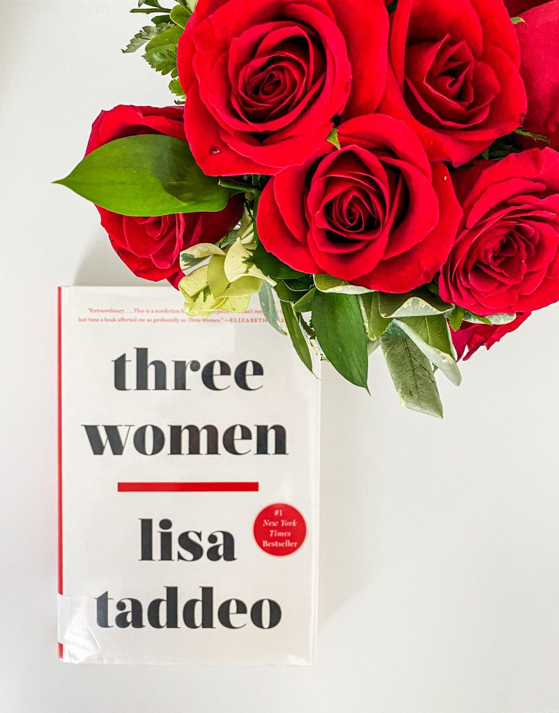 A white book titled Three Women by Lisa Taddeo pictured with a bouquet of red roses